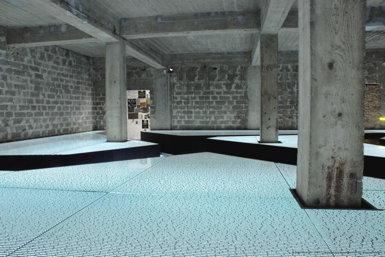 """Im """"Raum der Namen"""" werden alle namentlich bekannten im KZ Mauthausen Verstorbenen aufgelistet. Über 81.000 Namen sind auf horizontal liegende Glasflächen gedruckt, zwischen denen die BesucherInnen hindurchgehen."""