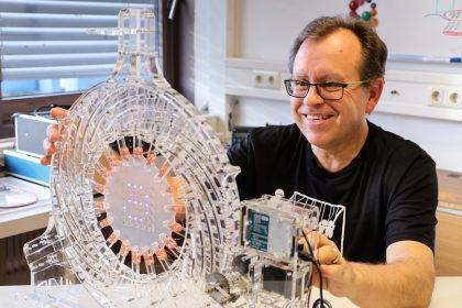 Der Experimentalphysiker Siegfried Bauer beschäftigt sich mit hoch aktuellen Themen wie dehnbarer und versteckter Elektronik, die sich überall anbringen lässt, aber auch mit künstlichen Muskeln. Hier ist er mit einer biaxialen Streckmaschine zu sehen – mit Lasercutter und 3D-Drucker gebaut. Die Maschine wurde bereits von einigen anderen Labors kopiert – dank der Veröffentlichung der detaillierten Bauanleitung. http://www.somap.jku.at/rss/