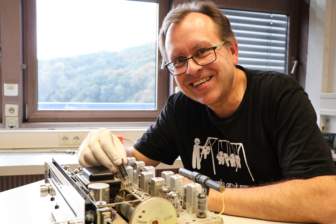 "Siegfried Bauer engaged in one of his hobbies, replacing a defective electron tube in an old steam radio. His T-shirt, a birthday gift from friends, says ""Physicists make great parents""."