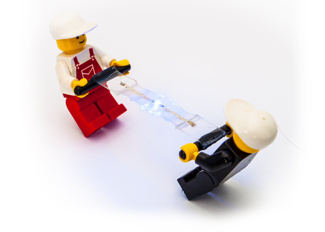 Simple works best: how can you best demonstrate stretchable electronics? Two Lego figures pull apart the soft material containing the electronics.