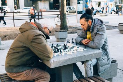 Alter und junger Mann spielen Schach im Freien auf einem Stadtplatz.