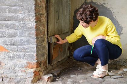 Die Historikerin Stephanie Weismann späht in einen Türspalt hinein in einem Innenhof in Lublin.