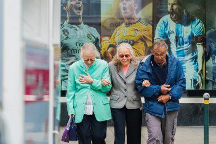 Drei ältere Menschen spazieren ineinander eingehängt die Straße entlang und lachen.