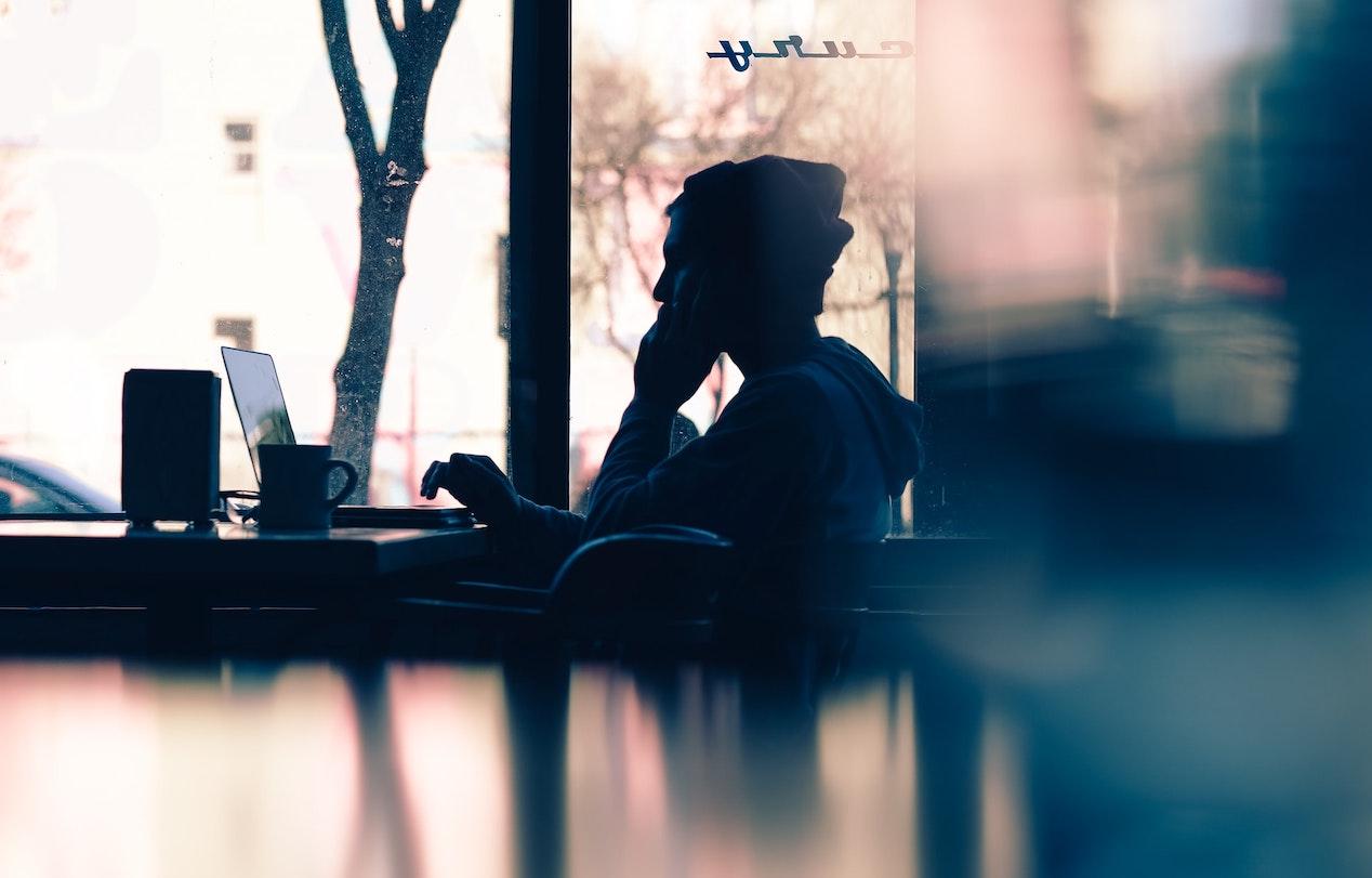 Junger Mann mit Mütze sitzt in einem Kaffehaus vor dem Laptop und arbeitet.
