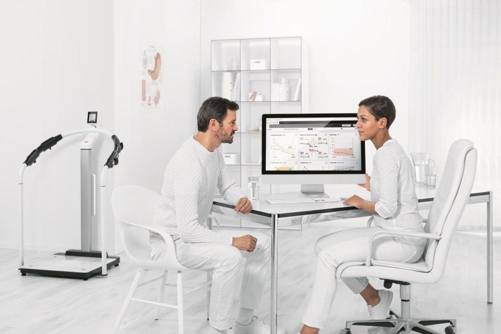 Eine Medizinerin und ein Mediziner sitzen am Schreibtisch vor einem Bildschirm mit Datenanalysen. Sie beraten sich.