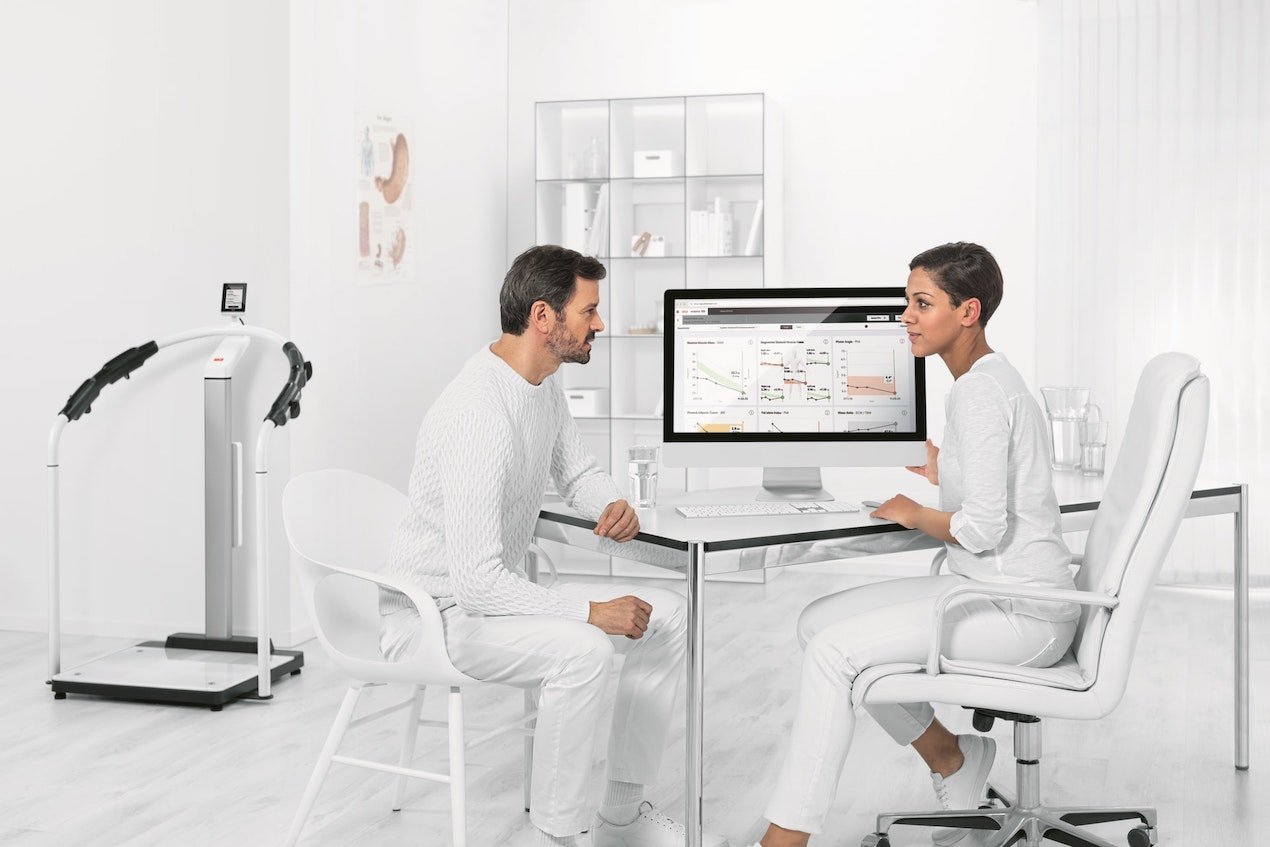 Two physicians discussing data analysis shown on their computer screen.