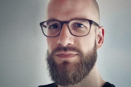Portrait of Jan Stupacher. Young man, bald head, brown beard and eye glasses, black T-shirt