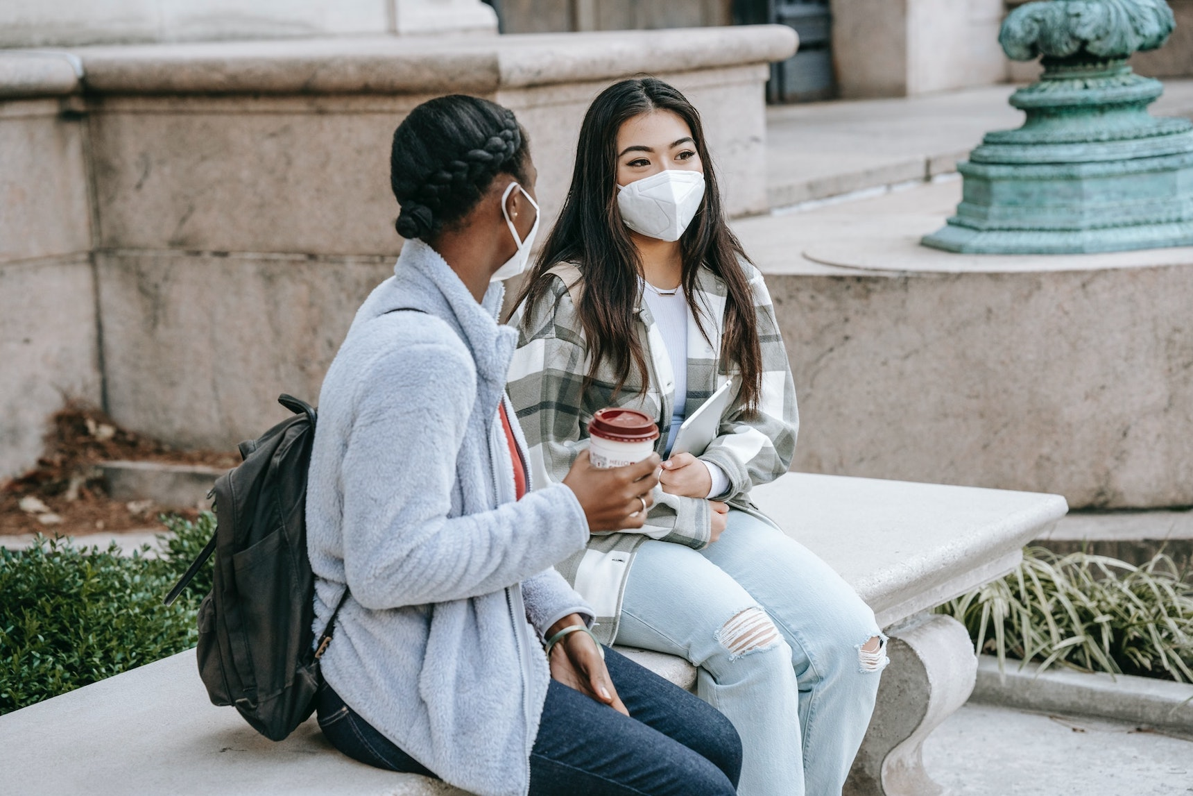 Two female students with face masks are chatting on a stone bench at university campus