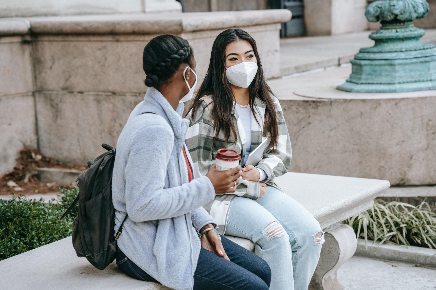 Zwei Studentinnen mit Mund-Nasen-Schutz unterhalten sich auf einer Steinbank am Campus einer Universität