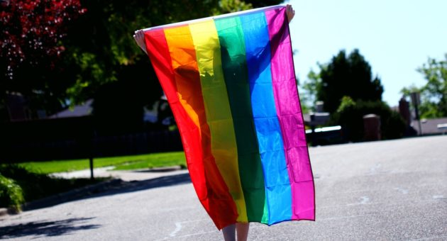 Young man walking along the street with rainbow flag on his back.