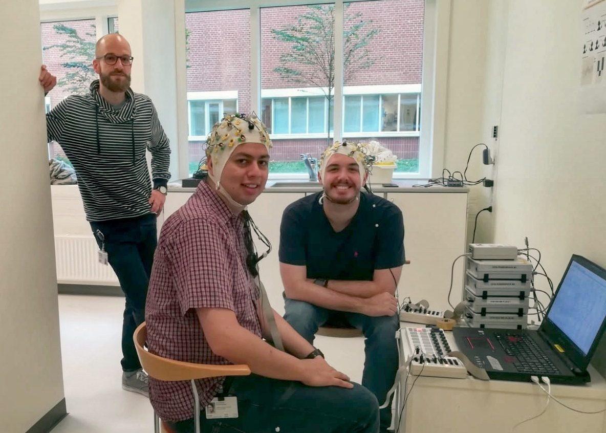 Vorführung eines der EEG-Paradigmen die am Center for Music in the Brain verwendet werden. Jan Stupacher im Hintergrund mit zwei Kollegen.