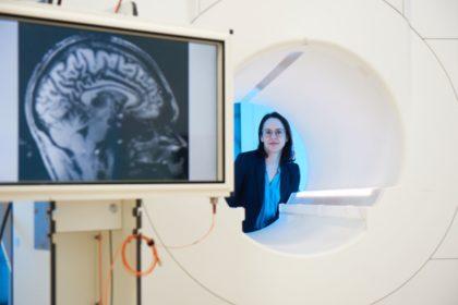 Junge Psychologin im Labor. Sie schaut durch die Öffnung eines Magnetresonanztomografen. Im Vordergrund links ist der Scan eines menschichen Gehirns zu sehen.