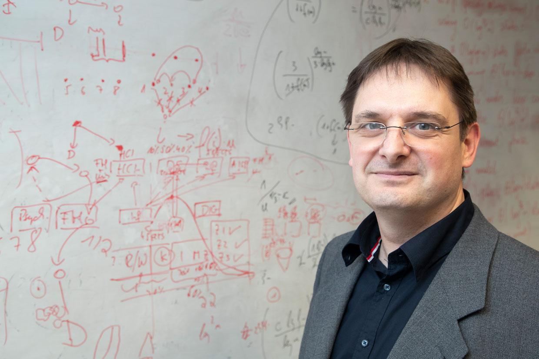 Porträt des Mathematikers Robert Elsässer vor Tafel mit Kurven und Berechnungen