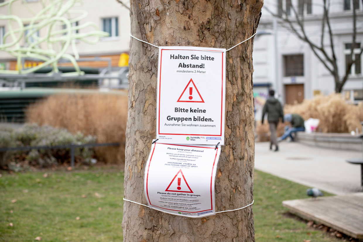 """Signs reading """"Please keep your distance!"""" and """"Please do not form groups"""" on a tree in a public park in Vienna are meant to remind people of the current corona measures."""