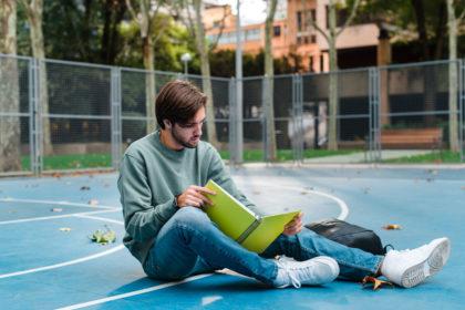 Junger Mann liest in einem Notizbuch, um zu lernen, auf einem Basketballplatz an einer Universität.