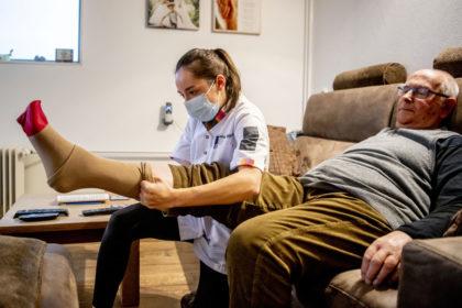 Eine Pflegerin zieht einem älteren Mann in seiner Wohnung einen Stützstrumpf über das Bein.